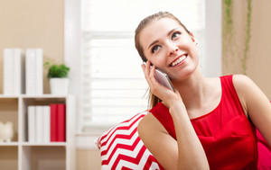 Happy young woman talking on her phone at home