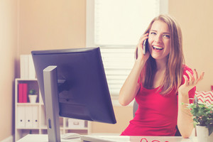 Happy young woman talking on her smart phone in her home office