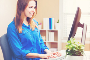 Happy young woman using a her computer in her home office