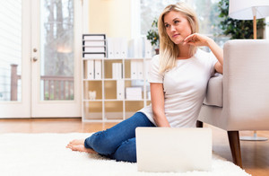 Happy young woman using her laptop at home