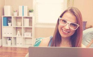 Happy young woman using her laptop on her couch at home
