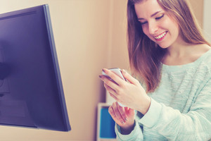 Happy young woman using her smart phone in her home office