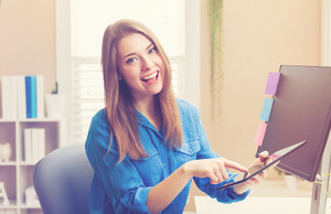 Happy young woman using her tablet computer in her home office