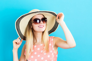 Happy young woman wearing a hat and sunglasses on a blue background
