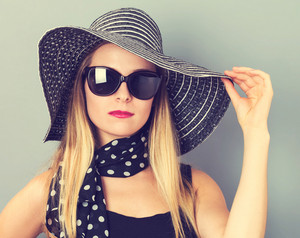 Happy young woman wearing a hat and sunglasses on a gray background