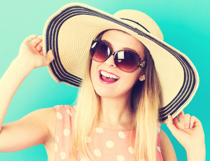 Happy young woman wearing a hat and sunglasses on blue background