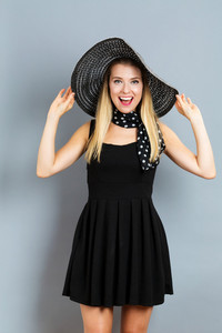 Happy young woman wearing a hat on a gray background