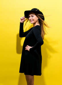 Happy young woman wearing a hat on a yellow background