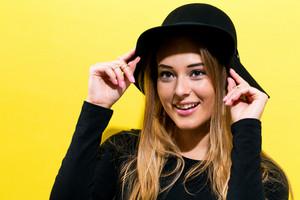Feliz, mulher jovem, desgastando um chapéu, ligado, um, experiência amarela