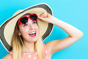 Happy young woman wearing a red heart sunglasses on blue background