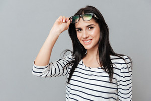 Happy young woman wearing eyeglasses over grey background. Look at camera.