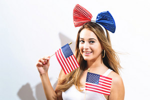 Happy young woman with American flags on the fourth of July