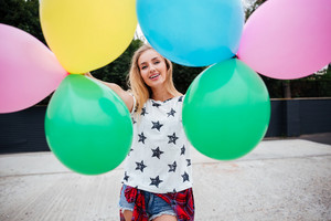 Happy young woman with colorful latex balloons outdoors