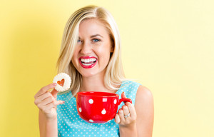 Happy young woman with cookie and coffee on a yellow background