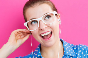 Happy young woman with earbuds on pink background