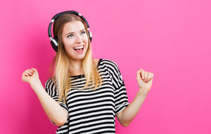 Happy young woman with headphone on pink background