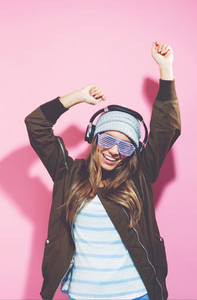 Happy young woman with headphones on a pink background