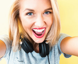 Happy young woman with headphones on a yellow background