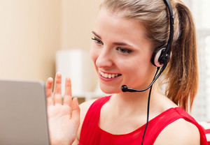 Happy young woman with headset talking on her laptop