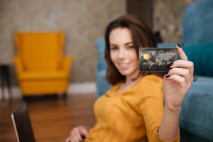 Happy young woman with laptop showing her credit card while sitting in the living room