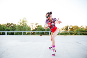 Happy young woman with lollipop standing on roller skates and showing peace sign