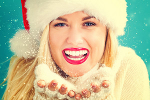 Happy young woman with Santa hat blowing snow