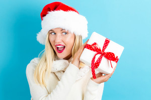 Happy young woman with Santa hat holding a Christmas present box