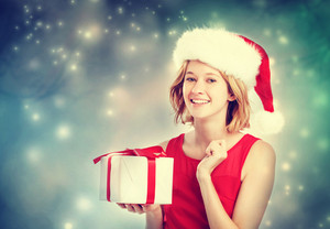 Happy young woman with Santa hat holding a gift box