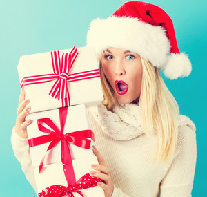 Happy young woman with Santa hat holding a stack of gift boxes