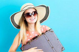 Happy young woman with travel theme on blue background
