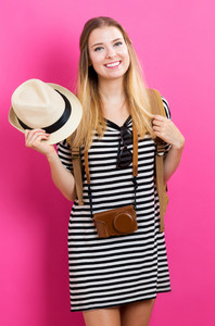 Happy young woman with travel theme on pink background