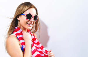 Happy young woman with USA national holiday accessories