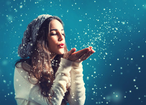 Happy young woman with winter clothes blowing snow