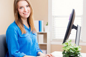 Happy young woman working on a computer in her home office