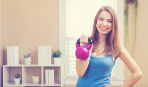 Happy young woman working out with a kettlebell in her house
