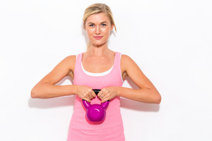 Happy young woman working out with a kettlebell