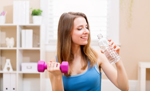 Happy young woman working out with dumbbells and drinking water