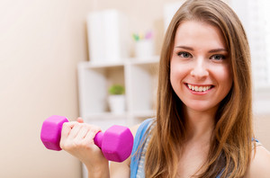 Happy young woman working out with dumbbells in her house