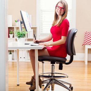 Happy young woman working with a pen stylus tablet in her home office