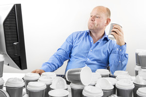 Hardworking business man drinks too much coffee
