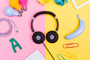 Headphones with objects on a pink and yellow background