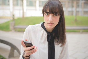 Headshot of a young beautiful brown hair businesswoman seated on a bench in a city park using a smartphone looking in camera - business, technology, communication concept