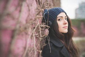 Headshot of young beautiful long hair girl laying on a wall in winter in the city listening to music with headphones, looking in camera - relaxing concept