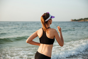 Healthy young woman in cap running on beach at the sunset