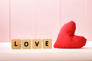 Heart cushion with love message on pink wooden board