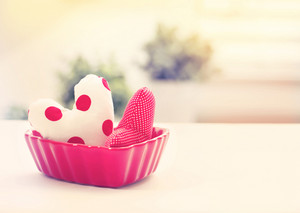 Heart cushions in a red heart dish on a white table