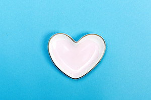 Heart shaped candy dish on a blue background