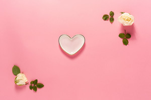 Heart-shaped dish with white rose frame on a pink background