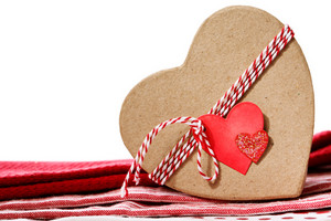 Heart shaped gift box with heart tag on red table cloth