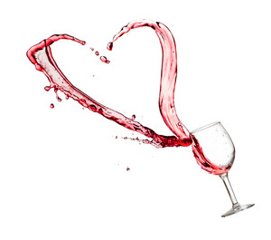 Heart splash from a glass of red wine isolated on white background